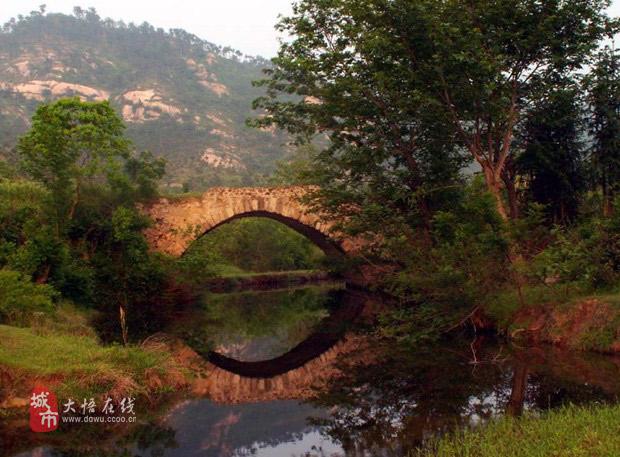 次,我们在一座柳树掩映的石拱桥下拍照.绿草如茵的河滩上,洁白的