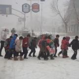 冰天雪地有关爱――二小老师看护小学生小心翼翼的走过冰滑道路
