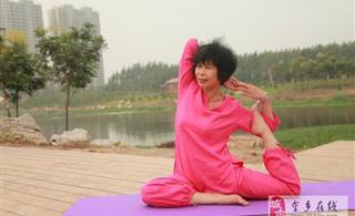 金济河畔九曲桥边练瑜伽的老太